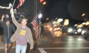 "Jeremiah Lee, 25, runs across the intersection of Shaw and Blackstone after the announcement of Bin Laden's death.  He said he had ""the need to celebrate with the rest of the country."""