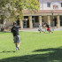 Eric Pugh, in white, catches a pass from Timothy Garcia while playing football in the free speech area. They practice and enjoy the green grass in between their classes.