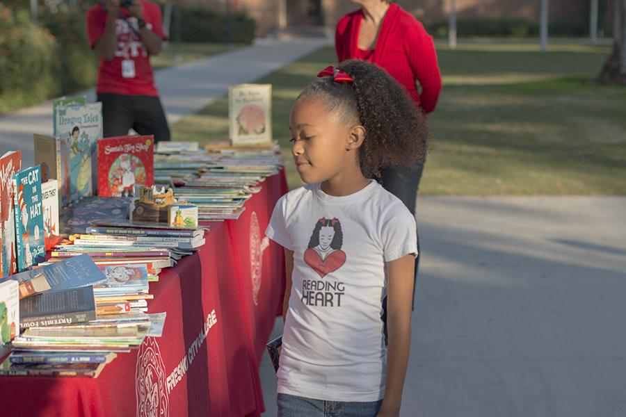 "On behalf of Reading Heart, her nonprofit book donation, 9-year-old Danay Ferguson gifts 500 books to the ""Hope for the Holidays"" program at Fresno City College, Friday, Nov. 13, 2015."
