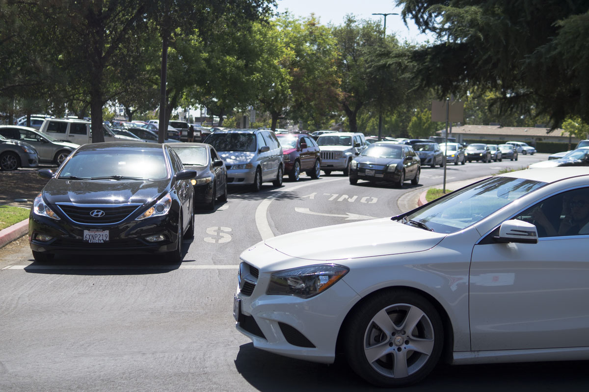 Cars line up on the road from the McKinley entrance as students attempt to find parking at Fresno City College on Aug. 15, 2016.
