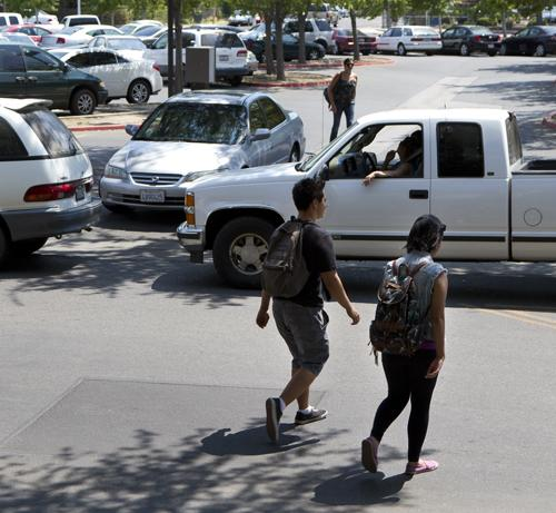 Students walk towards the parking lot while cars are stalled while waiting to exit Fresno City College on Tuesday, August 14., 2012 (Archive Photo)