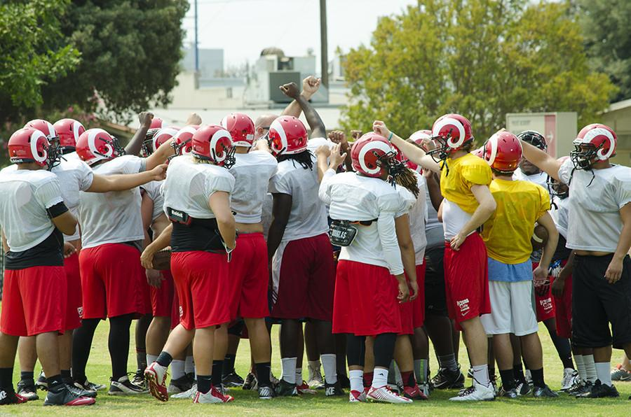 The+Fresno+City+College+football+team+huddles++for+support++before+their+practice.+