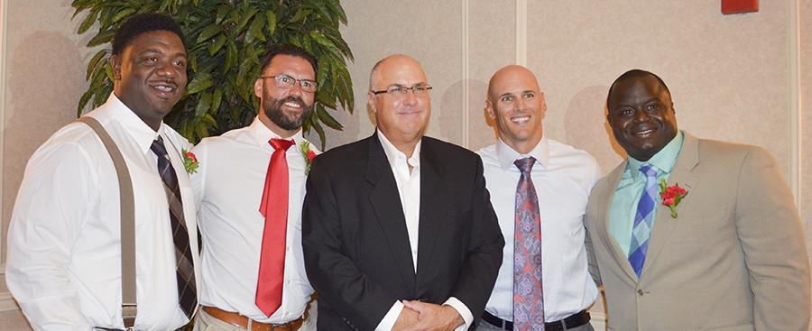 Former FCC football players (from left to right)) Tracey Hunt, Sean Soares, Matt Giordano, and Earl Charles stand with (Middle) Head Coach Tony Caviglia as they are honored at the 26th annual Wall of Fame.