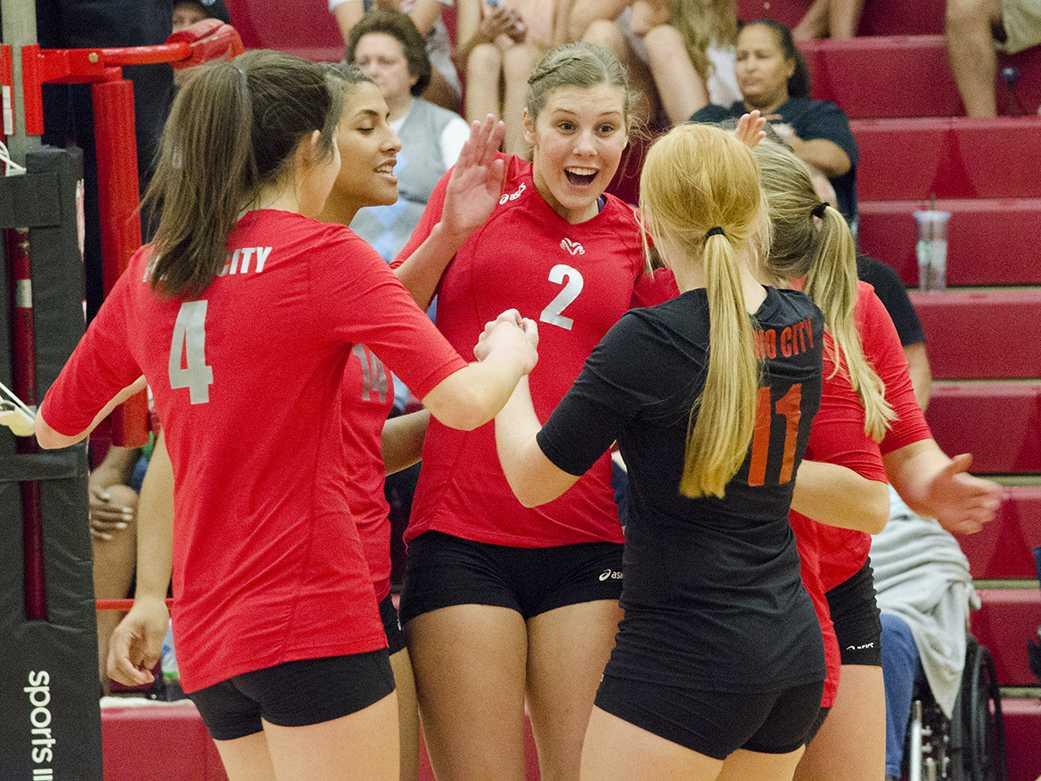 Jenna Goldsberry (4), Sydney Molander (2), and Carly Kosinski (11) celebrate on the court.