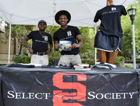 Femi Olukanni Jr. (right) and Emerald Thomas  (left) display merchandise from Select Society Clothing Brand at  the FCC Art Hop Oct. 1,2015.