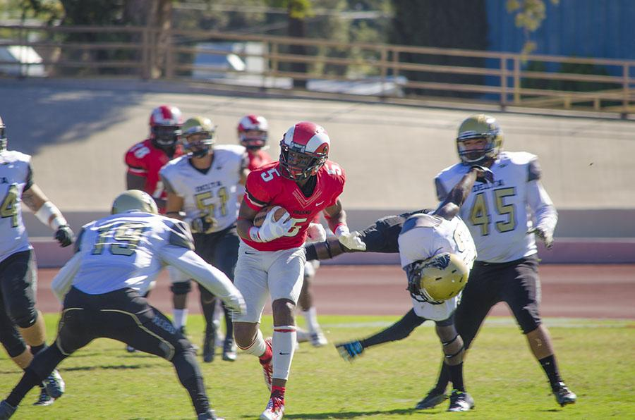 Wide receiver James Whitfield, of Fresno City College, looks for an opening and evades running back Javaughn Iverson of San Joaquin Delta College at Ratcliffe Stadium at the homecoming game Oct. 31, 2015.