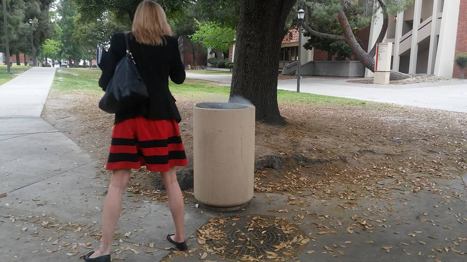 A woman looks into a trash can that had smoke rising from it on Thursday, April 7, 2016.