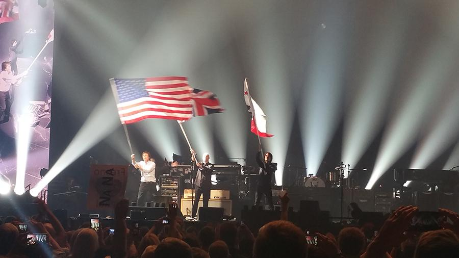 Paul McCarney and his band mates wave flags of the United States, the United Kingdom and of the California State Flag at the Savemart Center in Fresno, California on April 13, 2016.