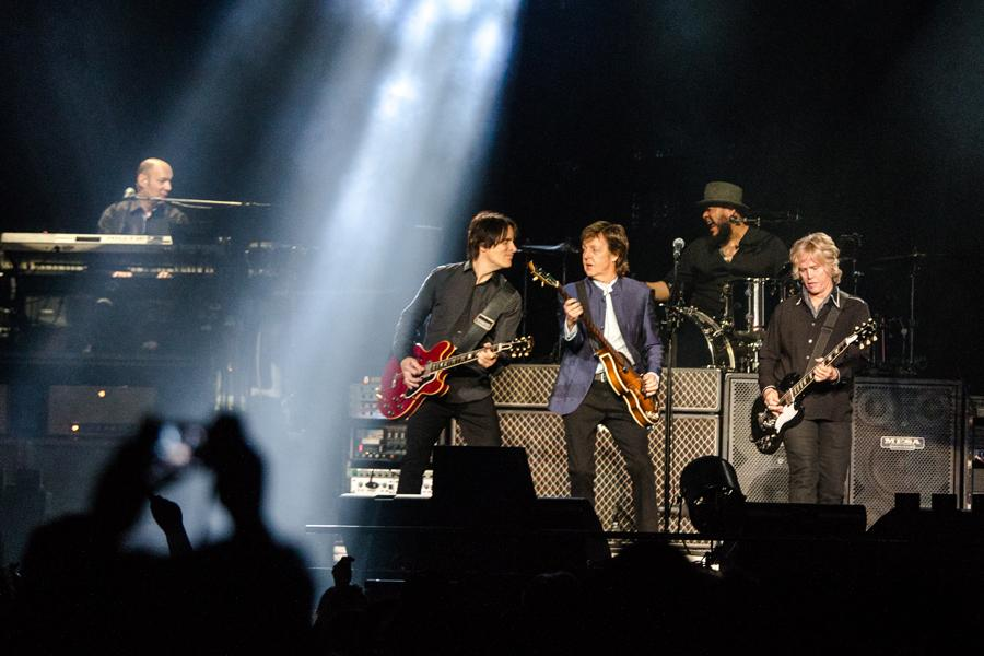 Paul McCartney and his band performing