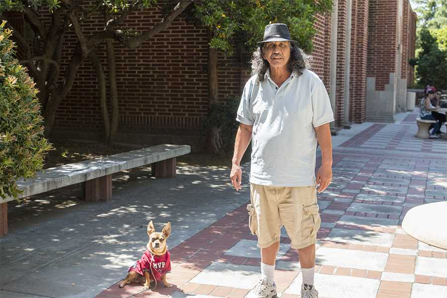 Larry Rodriguez stands next to his dog, Zapata outside the Fresno City College Library building on April 13, 2016. Rodriguez says his pet dog helps him get through college. Rodriguez and Zapata have become familiar faces on campus.
