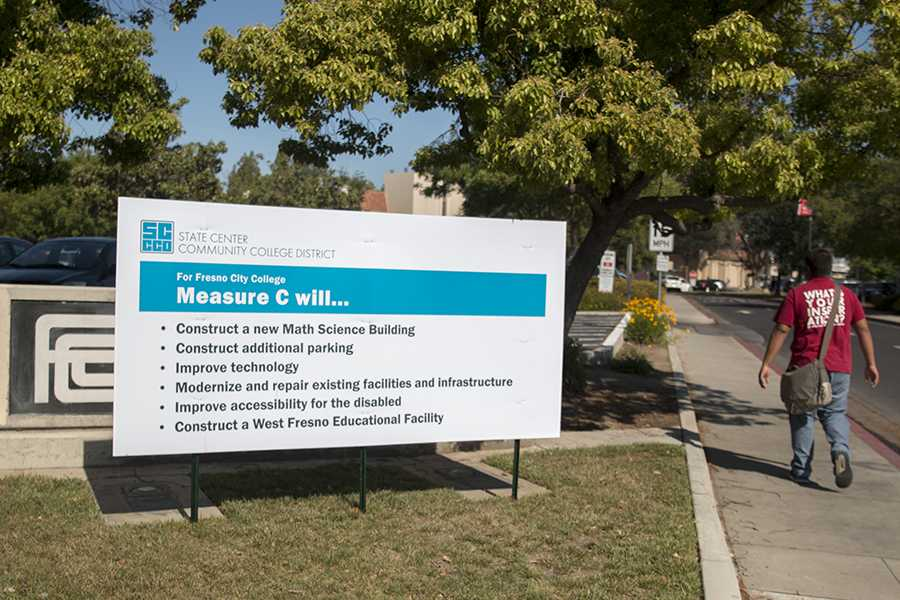 A student walks near a State Center Community College District billboard promoting Measure C at the southeast entrance to Fresno City College on April 18, 2016.