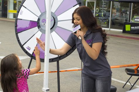 "Kimberly Marquez high fives a young listener during a ""remote"" for Q97.1 FM at a Metro PCS store in Fresno, Calif. on April 7, 2016"