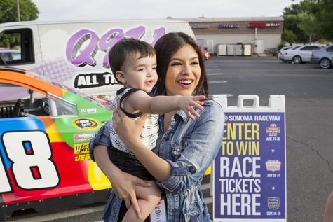 "Kimberly Marquez stops to take a picture with a young listener during a ""remote"" for Q97.1 FM at Save Mart in Clovis, Calif. on May 4, 2016"