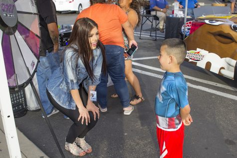 "Kimberly Marquez take a moment to talk with a young listener during a ""remote"" for Q97.1 FM at Save Mart in Clovis, Calif. on May 4, 2016"