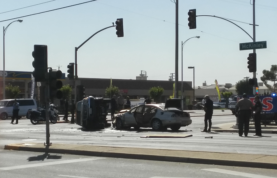 Police examine a crash that left two vehicles damaged, one overturned, at the McKinley and Blackstone avenues near Fresno City College.