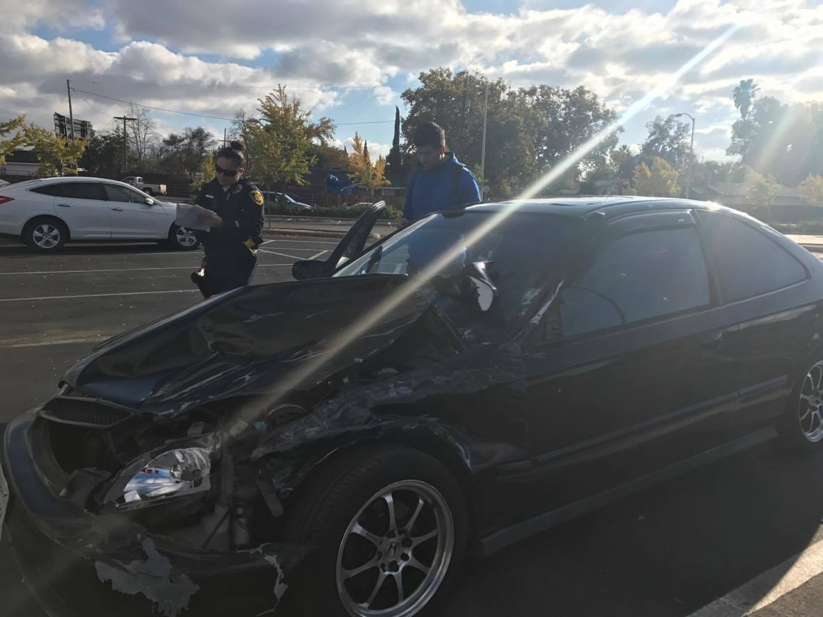 A State Center Community College District police officer writes information after Fresno City College Jesus Anguiano crashed into three cars on Monday, Nov. 21, 2016.