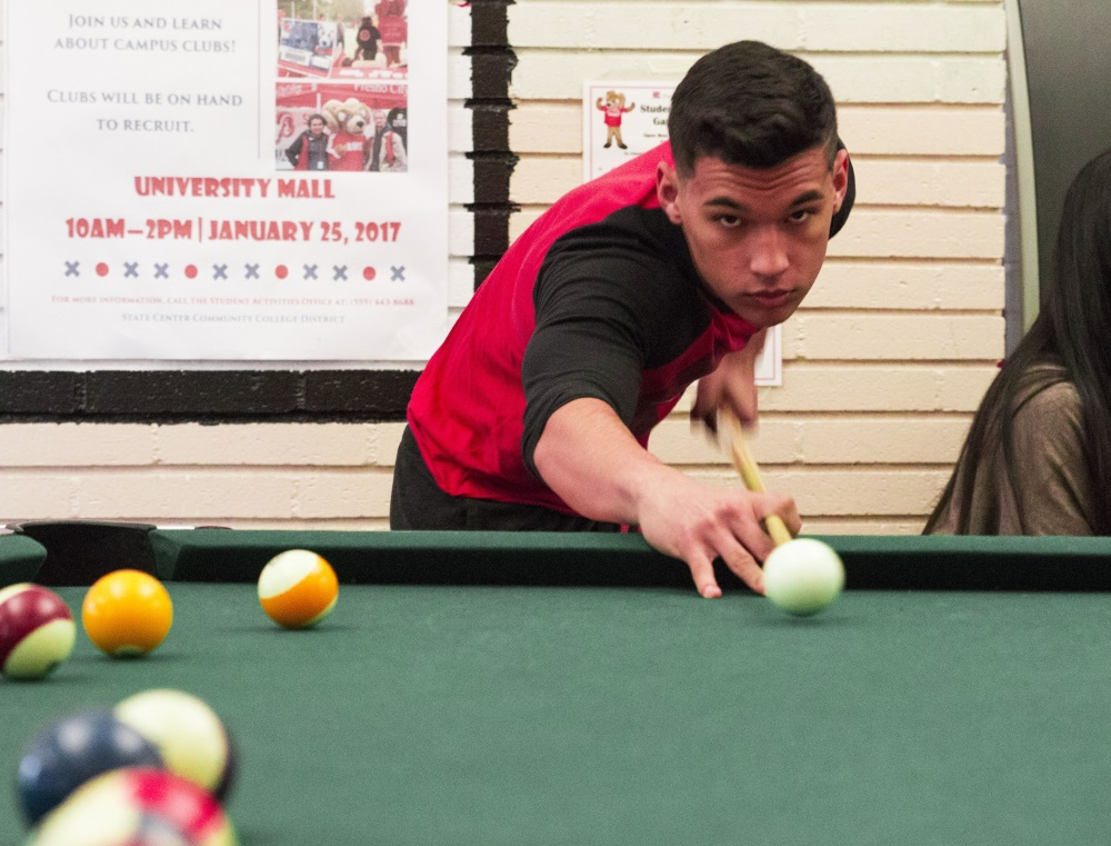 Joshua Alvarado making his shot into the corner pocket  in the game room at Fresno City College on Jan. 23, 2017.