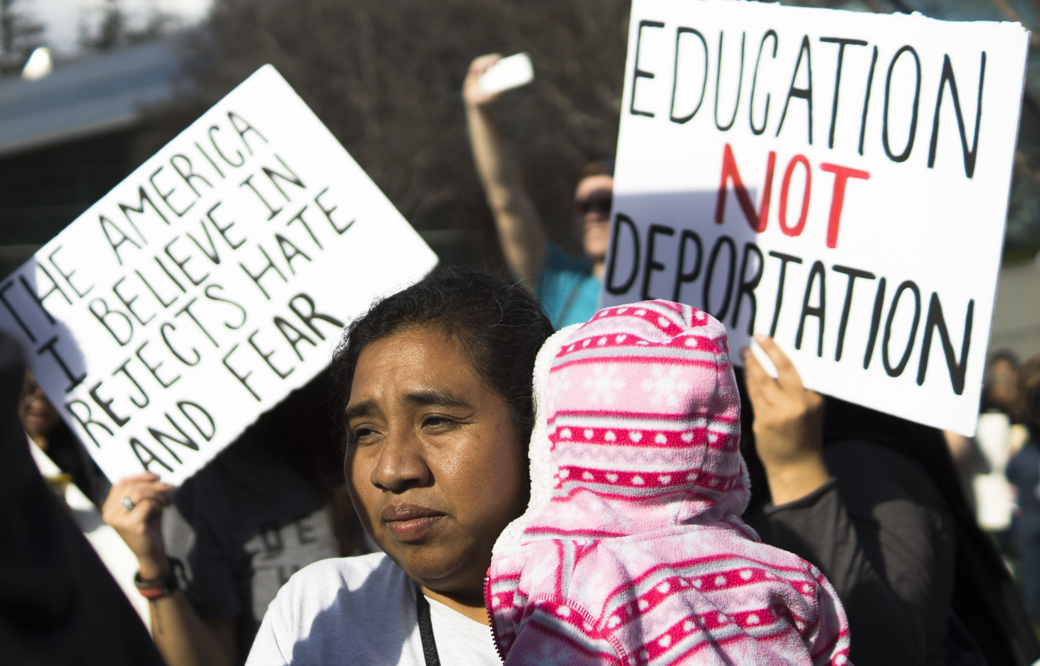 Monica Lopez and her daughter, Ruby, look onto the crowd of protesters at Fresno City Hall for the