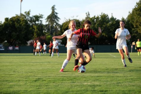 Franki Navarro covers the ball from Cyprus College players during their home opener on Wednesday, Sept. 6, 2017.