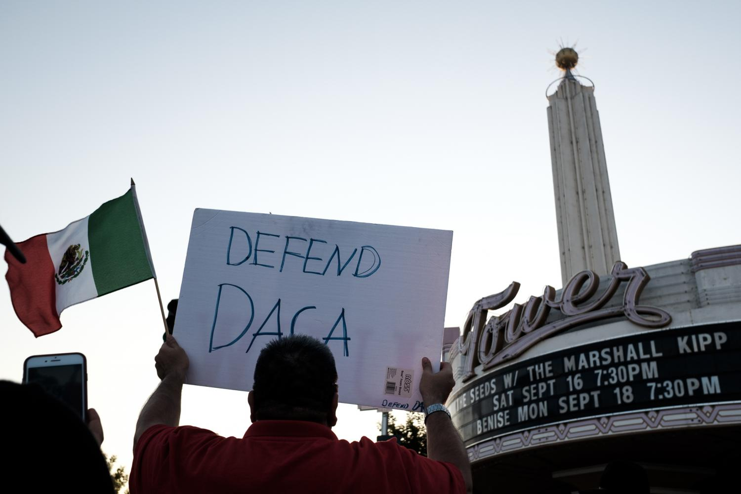 A+protester+holds+up+a+sign+as+they+walk+down+Olive+avenue+for+the+%22March+to+Defend+DACA%22+at+Fresno%27s+Tower+District+on+Sunday%2C+Sept.+15%2C+2017.