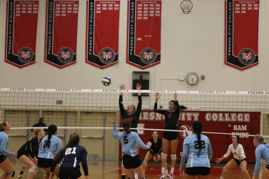 Fresno City College middle blocker Abbey Briggs and outside hitter Makayla Cervantes jump to make a block during a game against Cerro Coso Community College on Friday, Nov. 3, 2017.