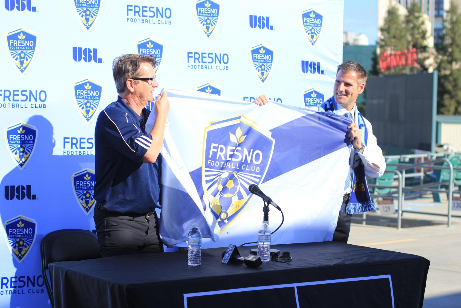 General Manager Frank Yallop (left) and Head Coach Adam Smith (right) hold a Fresno FC flag during the official presentation of Smith as head coach at the Chuckchansi Park on Thursday, Nov. 9, 2017.