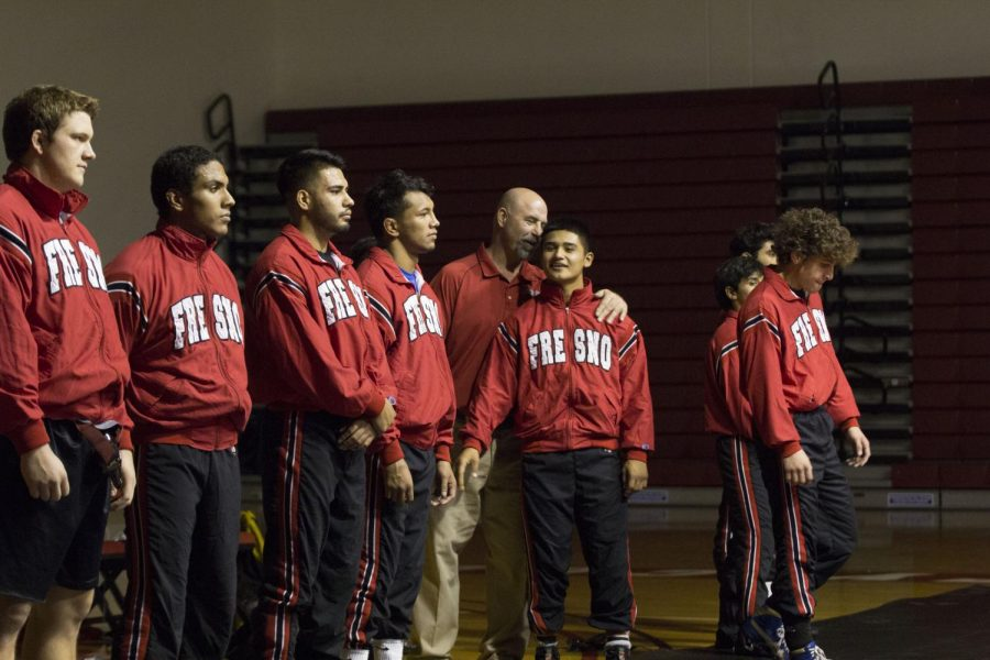 Fresno City College wrestling head coach Paul Keysaw (center) talks to his wrestler before a duel at home.