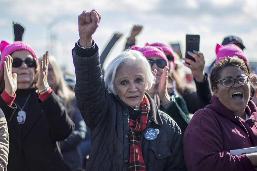 Patricia Johnson raises her fist in protest at the Women's March in Fresno River Park area on Saturday Jan. 20, 2018.