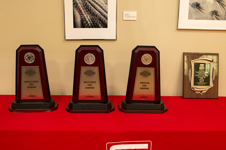 The three state championship trophies for women's soccer; men's soccer and wrestling alongside coach Keysaw's coach of the year award.