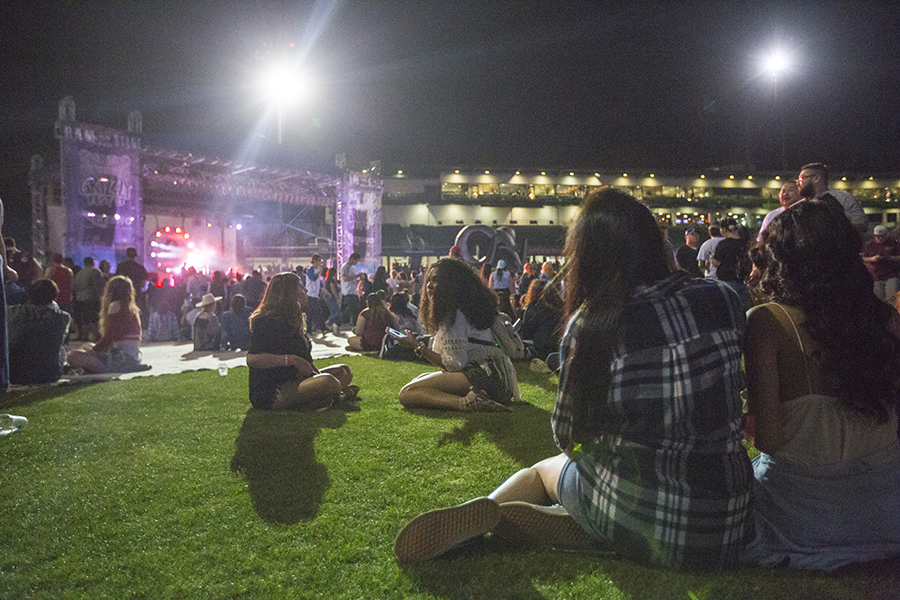 A crowd sits on the grass at Grizzly Fest 2017, Saturday night on April 29, 2017. Participants sat on the grass to enjoy music, food and drinks or when a break was needed.
