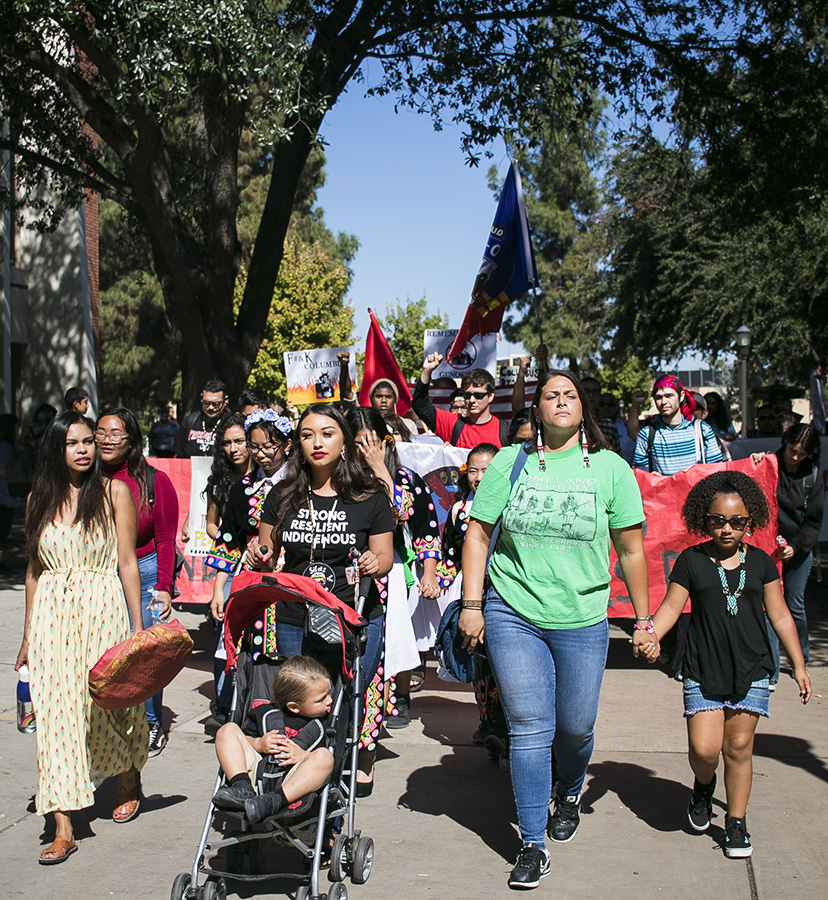 Students hold up signs and march to the fountain area to celebrate Indigenous people's Day on Monday, Oct. 8, 2018.
