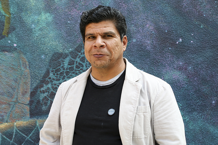 Fresno City College art professor Ricardo Rivera in front of a mural in Fresno City College on Tuesday, Nov. 20, 2018.  Rivera poses social commentary on racism, classism and discrimination through his artwork.