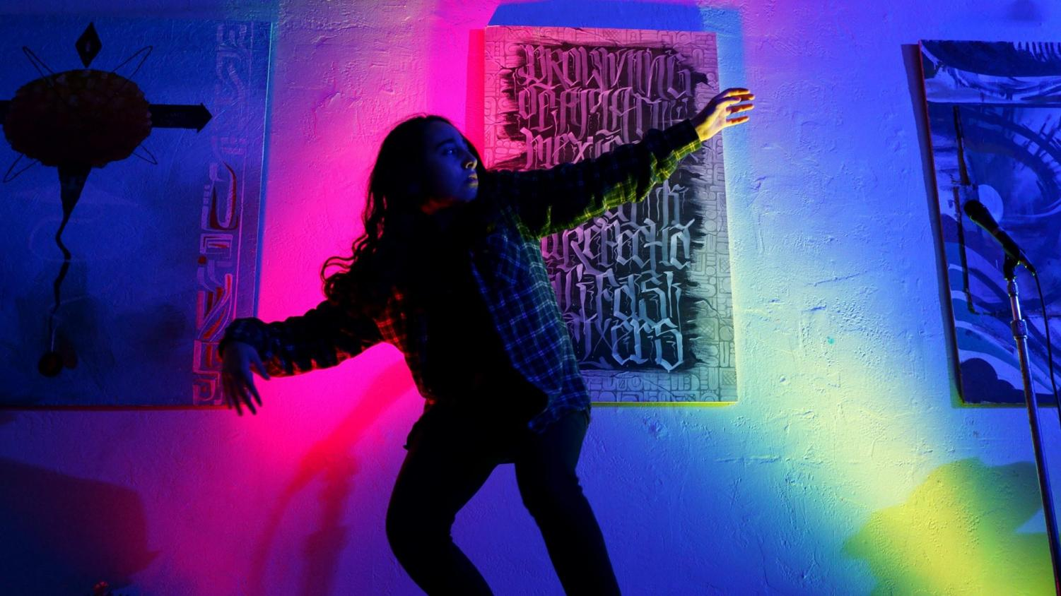Dhani Del Toro dances in a dark lit room.