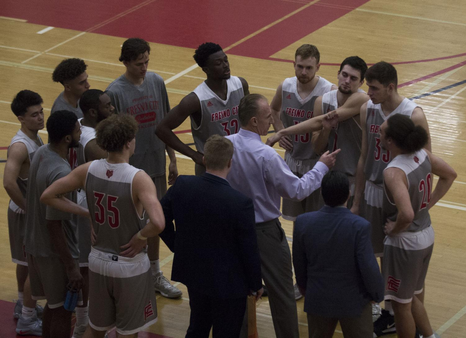 The Rams Men's basketball team surrounds head coach Ed Madec as he prepares them for the second half of their round 2 regional playoff game against Sacramento City College on March 2, 2019.