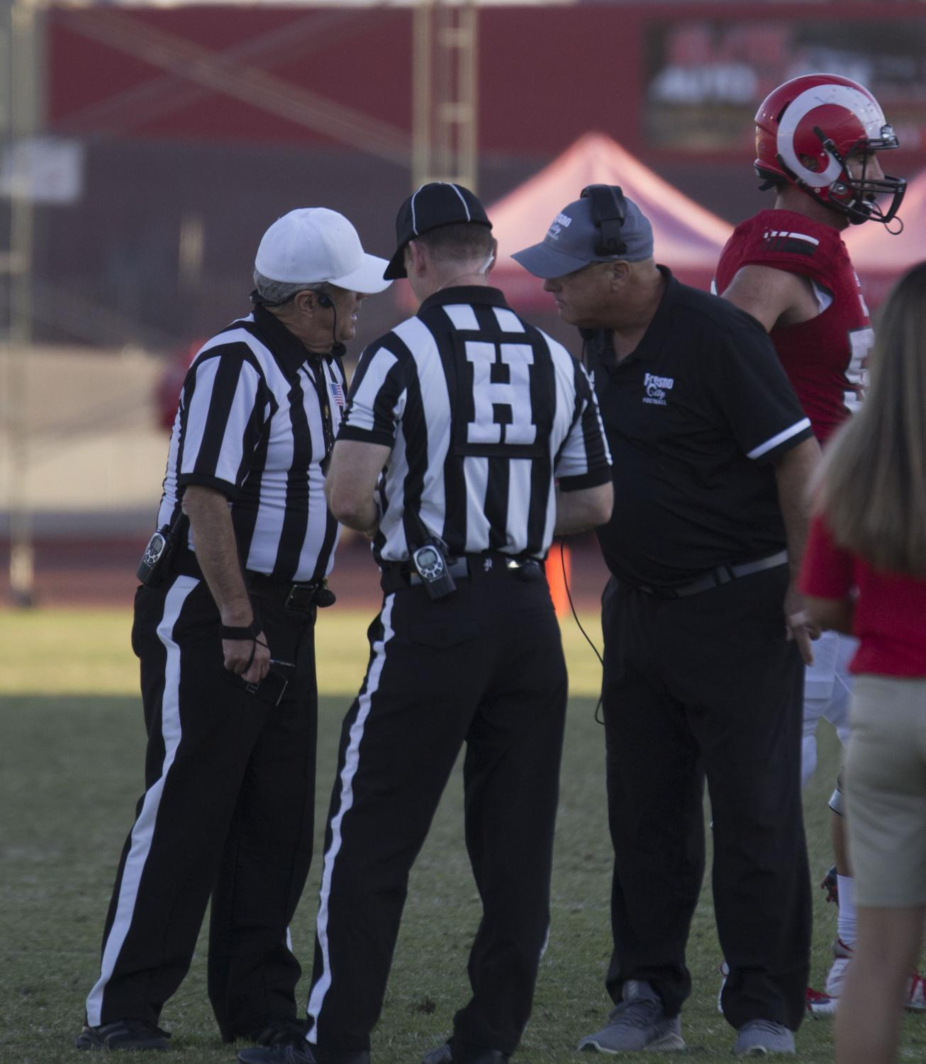 Rams head coach Tony Caviglia meets on the sidelines with referees during a timeout in the Rams' game against American River College on Oct. 5, 2019. The Rams went on to lose the game by a score of 9-3.