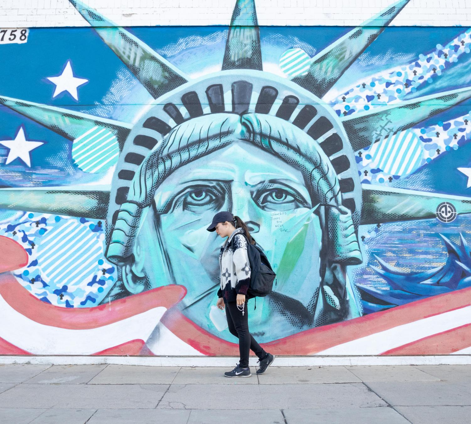 Dreamer+Jackie+Garcia+holds+items+that+represent+her+journey+from+Mexico+to+the+U.S.+in+front+of+the+Statue+of+Liberty+mural+at+the+Amvets+in+Downtown+Fresno+on+Saturday%2C+Nov.2%2C+2019.