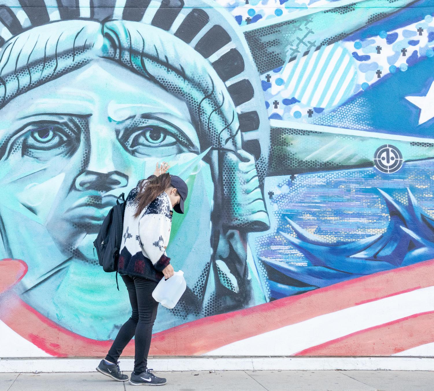 Dreamer+Jackie+Garcia+holds+items+that+represent+her+journey+from+Mexico+to+the+U.S.+in+front+of+the+Statue+of+Liberty+mural+at+the+Amvets+Building+in+Downtown+Fresno+on+Saturday%2C+Nov.2%2C201