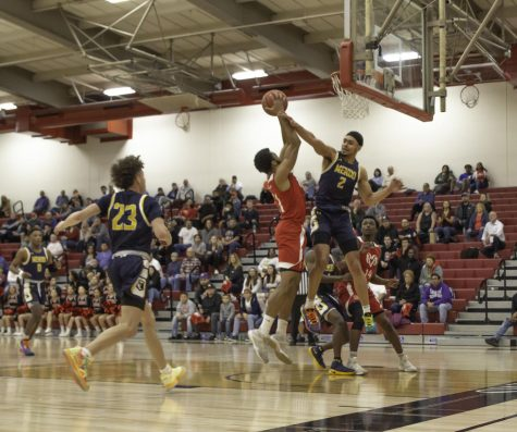Sophmore guard Jeshawn Bruner powers through freshman wing Alex Rojas during the Rams