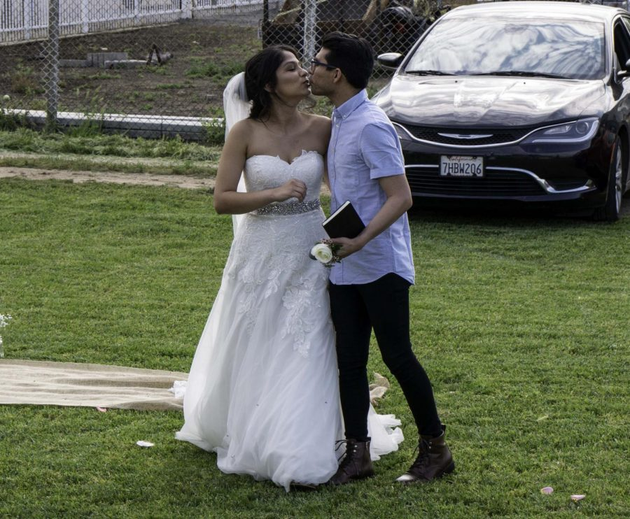 The newly wedded Ethan and Alyssa Larios share a kiss on April 17.