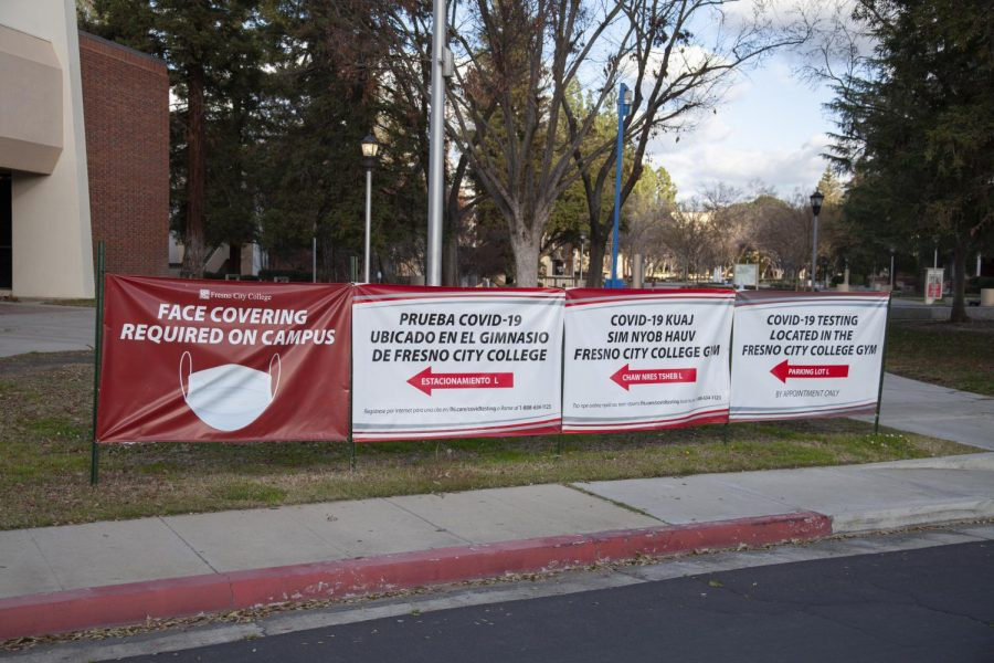 Signs requiring face covering line the edge of the FCC campus.